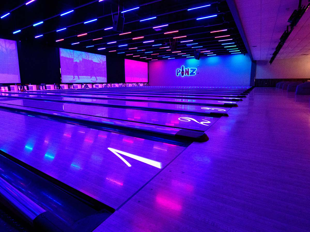 Projection screens and lighting fixtures over bowling lanes