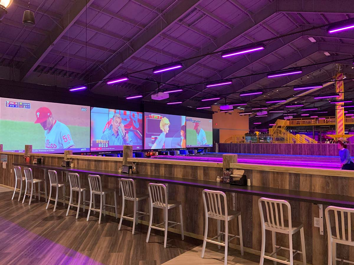 Projection screens and Versalamp fixtures over bowling lanes