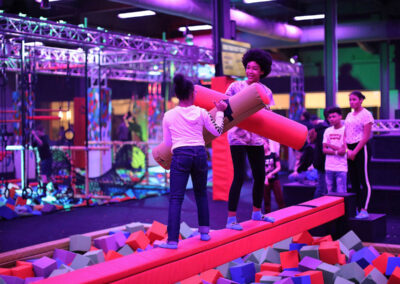 Guests playing in a foam pit with UV lighting